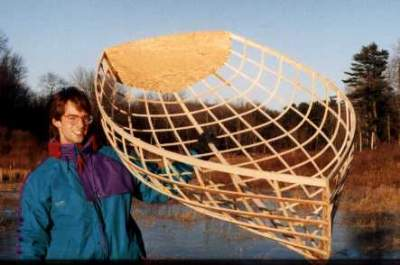 Grandson, Ryan, holds the frame of a Westport Dinghy 8 that he built with Platt